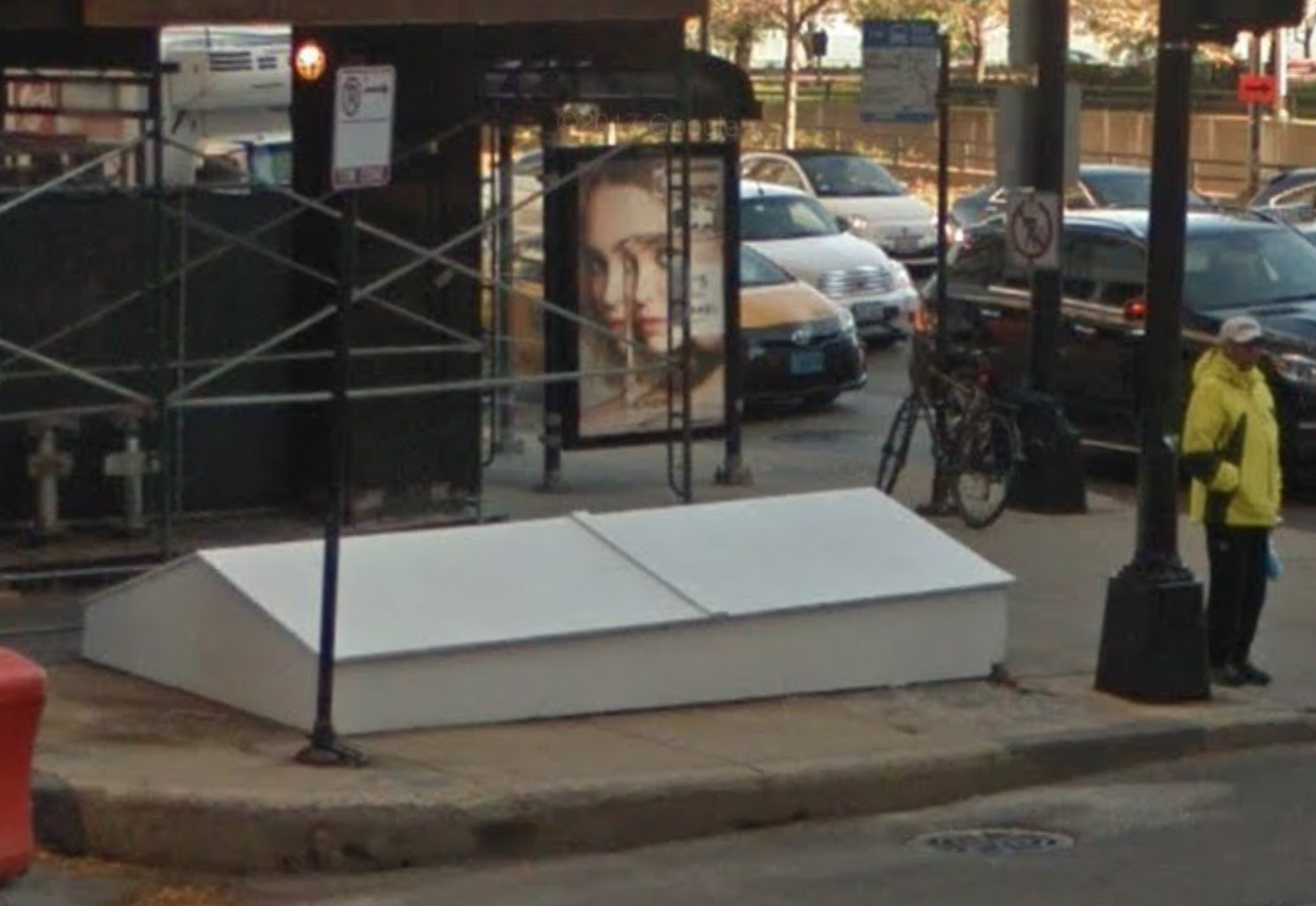 """Wooden """"doghouse"""" covering the tunnel entrance on the corner of Oak Street and Michigan Avenue (via Google Streetview)"""
